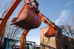 Cubo anaranjado del excavador en el cielo azul Foto de archivo
