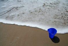 Cubo azul en la playa Imagenes de archivo