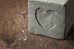 Cubo con el corazón de la arcilla en superficie de madera Fotos de archivo libres de regalías