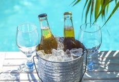 Cubo con la cerveza y el hielo en una tabla de madera al lado de la piscina fotos de archivo libres de regalías