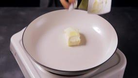 Cubo da manteiga que derrete na bandeja, preparação para cozinhar vídeos de arquivo