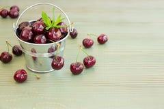 Cubo de cerezas con las hojas de menta Imagen de archivo libre de regalías