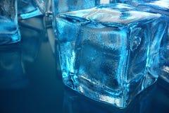 cubo de gelo da rendição 3D no fundo azul do matiz Cubo congelado da água Imagem de Stock