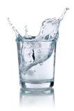 Cubo de gelo que espirra no vidro com água Foto de Stock Royalty Free