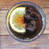 Cubo de hielo cortado del limón con la bebida en el vidrio Fotografía de archivo
