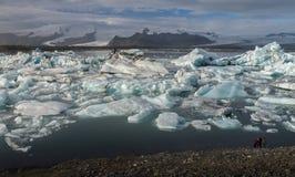 Cubo de hielo en la laguna glacial de Jokulsarlon con la montaña de la nieve Imagenes de archivo
