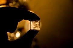 Cubo de hielo en su mano Foto de archivo libre de regalías
