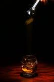 Cubo de hielo que cae en el whisky Imagen de archivo libre de regalías