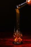 Cubo de hielo que cae en el whisky Imágenes de archivo libres de regalías