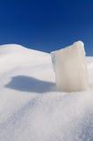 Cubo de hielo sólido, nieve acumulada por la ventisca y cielo azul despejado Foto de archivo libre de regalías