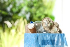 Cubo de la basura con basura en fondo borroso imagen de archivo libre de regalías