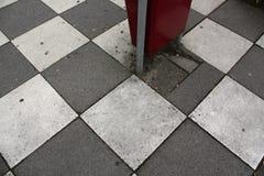 Cubo de la basura en la calzada peatonal sucia imagenes de archivo