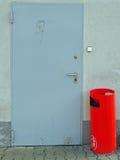 Cubo de la basura rojo delante de una puerta sucia Imágenes de archivo libres de regalías