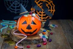 Cubo de la linterna de Halloween Jack o que desborda con el caramelo, decoraciones fantasmagóricas de Halloween en el fondo, espa Fotografía de archivo libre de regalías