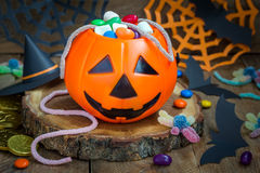 Cubo de la linterna de Halloween Jack o que desborda con el caramelo, decoraciones fantasmagóricas en el fondo horizontal Foto de archivo