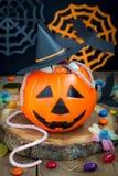 Cubo de la linterna de Halloween Jack o que desborda con el caramelo, decoraciones fantasmagóricas en el fondo, vertical Fotos de archivo