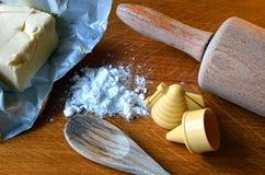 Cubo de la mantequilla, de los moldes del caramelo y del azúcar de formación de hielo en la tabla de madera Imagen de archivo