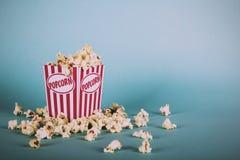 Cubo de las palomitas contra un filtro retro del vintage azul del fondo Imagen de archivo libre de regalías