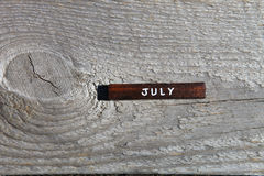 Cubo de madeira com o nome do mês na placa idosa julho Fotografia de Stock Royalty Free
