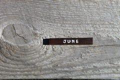 Cubo de madeira com o nome do mês na placa idosa junho Fotos de Stock Royalty Free