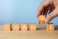 Cubo de madeira da aleta da mão com mudança da palavra ao crescimento o da carreira da possibilidade Fotos de Stock Royalty Free