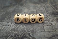 Cubo de madera con el blog de la palabra y vlog en fondo oscuro fotos de archivo