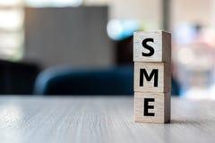 Cubo de madera con empresa media del texto de la PME pequeña en fondo de la tabla Conceptos financieros, del márketing y del nego imagenes de archivo
