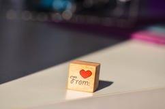 Cubo de madera con la inscripción escrita mano del corazón con el corazón rojo Fotos de archivo libres de regalías