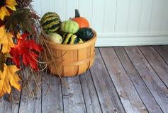 Cubo de madera con las calabazas y las hojas Foto de archivo libre de regalías