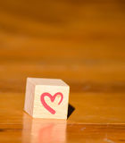 Cubo de madera con una mano escrita el corazón rojo Foto de archivo libre de regalías