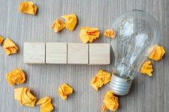 Cubo de madera vacío y papel desmenuzado con la bombilla en fondo de madera de la tabla IDEA, creativo, innovación, imaginación,  imágenes de archivo libres de regalías