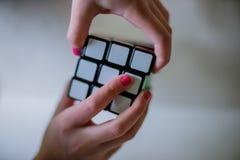 Cubo de Rubiks da terra arrendada das mãos foto de stock royalty free