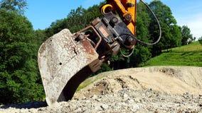 Cubo de un excavador en un emplazamiento de la obra foto de archivo