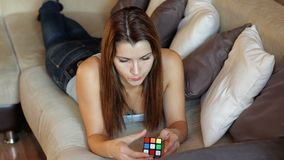 Cubo del ` s de Rubik La mujer hermosa juega con un cubo del ` s de Rubik La muchacha está intentando montar un cubo del ` s de R almacen de video