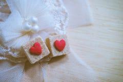 Cubo dello zucchero bruno decorato da poco cuore rosso su pizzo pastello Fotografia Stock