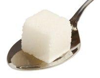 Cubo di zucchero bianco sul cucchiaio Immagini Stock Libere da Diritti