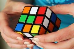 Cubo mágico del ` s de Rubik en las manos imagenes de archivo