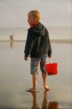 Cubo marchitado muchacho joven en la playa Foto de archivo