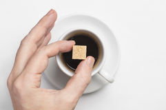 Cubo maschio dello zucchero di canna della tenuta della mano sopra la tazza di caffè nero contro la vista superiore del fondo bia Immagini Stock Libere da Diritti