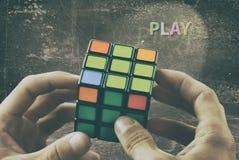 Cubo nas mãos de um homem na perspectiva de uma parede do vintage Jogue o jogo imagens de stock royalty free