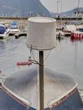 Cubo plástico invertido sobre un barco dado vuelta en puerto Imagenes de archivo