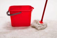 Cubo rojo con la fregona de la limpieza Imagenes de archivo