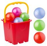 Cubo rojo de la playa con las bolas coloreadas Fotos de archivo libres de regalías