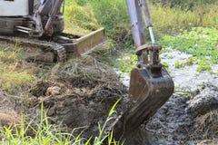 Cubo sucio de fango de excavación de la retroexcavadora y mala hierba en un canal Imagen de archivo libre de regalías