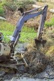 Cubo sucio de fango de excavación de la retroexcavadora y mala hierba en un canal Foto de archivo libre de regalías