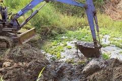 Cubo sucio de fango y de mala hierba de excavación de la retroexcavadora Fotografía de archivo libre de regalías
