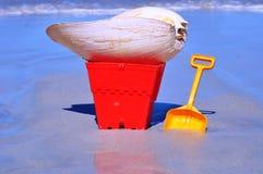 Cubo y espada con la cáscara grande del cono en la playa Imágenes de archivo libres de regalías