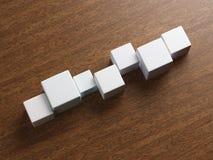 Cubos blancos en la tabla Fotos de archivo