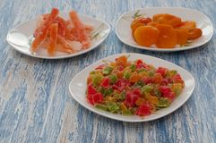 Cubos cristalizados do abacaxi em um prato branco em uma tabela de madeira Foto de Stock