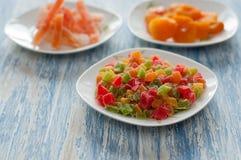 Cubos cristalizados do abacaxi em um prato branco em uma tabela de madeira Fotografia de Stock